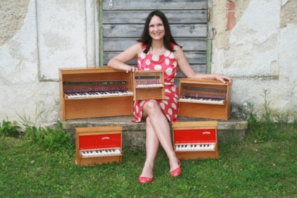 Isabel with her collection of Michelsonne toy pianos
